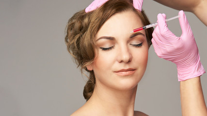 Face needle injection. Young woman cosmetology procedure. Doctor gloves