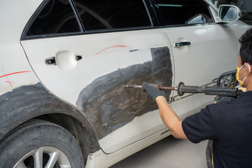 Car body work after the accident by preparing automobile for painting during repair