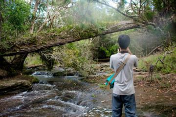 traveler take a photo of waterfall at Phu Kra Dueng National Park, Loei Thailand