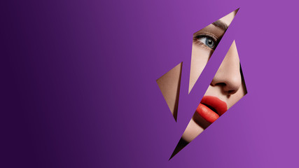 Beautiful woman face in purple paper frame. Plump red lips, blue eyes and clear skin. Fashion and beauty, close up portrait Wall mural