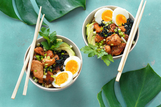 Two poke bowl fried rice chicken fillet eggs top view Asian food