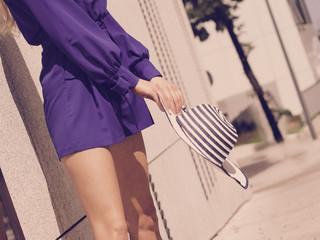Woman wearing purple dress holding sun hat