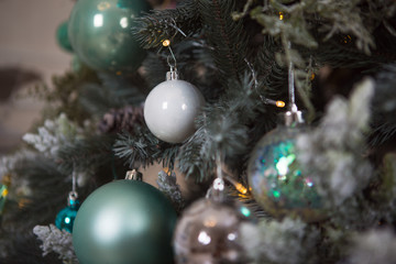 Christmas toys on a green artificial Christmas tree in a gentle style and gold lights garlands. Green, white and blue glass cones and balls decorate the spruce, close-up.