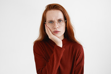 Human reaction, emotions and feelings. Picture of beautiful student girl with ginger hair frowning, having perplexed look, resting cheek on her hand, bored with tedious lecture or conversation