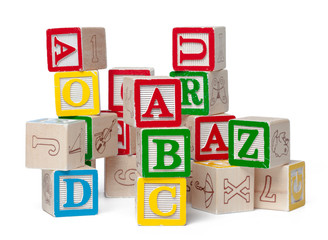 Colorful alphabet blocks stacked in a mess isolated on white background