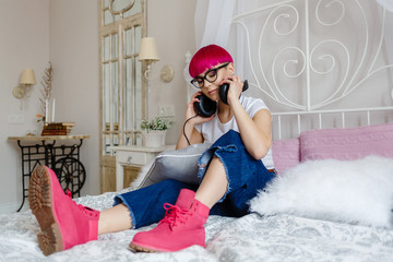 girl with pink hair listens to music and rests on the bed
