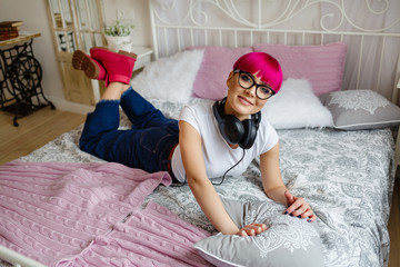 stylish girl with short pink hair listens to music on the bed in shoes
