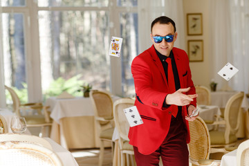illusionist in red suit shows focus. Magician in bright suit. a playbill of a magician and an illusionist