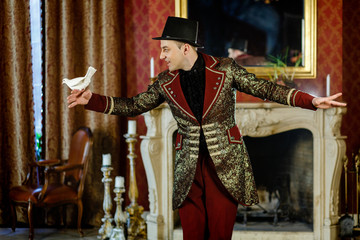 an illusionist is holding a dove in his hands. The magician shows a performance