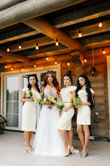 the red-haired bride is standing on the veranda of the house together with the bridesmaids in yellow dresses