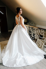 bride with black hair in a beautiful long dress is standing with her back and looking at the camera