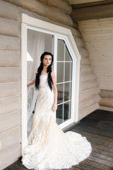 .young slender bride with dark hair stands on the window background