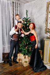 A young family in New Year costumes stands near a Christmas tree