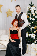 A man holds his wife's shoulders in white room near christmas tree