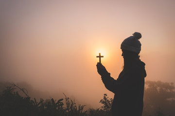 Silhouette of christian young woman praying with a  cross at sunrise, Christian Religion concept background.