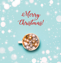 Minimalistic Christmas concept. Christmas decorations in cup on blue background. Top view, flat lay. Merry Christmas Text. Bright and festive