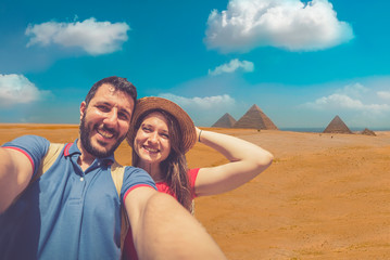 Young Couple taking selfie photo in front of the Great Pyramids of Giza, Egypt