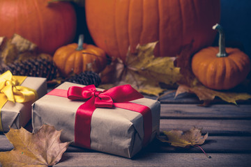 leaves and pumpkin with Halloween gift box on background. Autumn season image composition