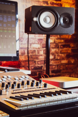 recording studio equipment. computer, midi keyboard synthesizer, loudspeakers, mixing console