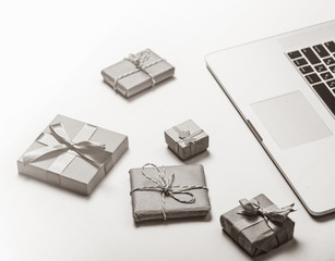 beautiful gifts of different sizes and cool laptop on white background . Image in black and white color style