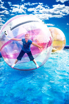 Young girl standing inside a floating water walking ball.