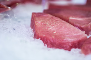 A pink, juicy, appetizing fish fillet lies on the ice, awaiting cooking.