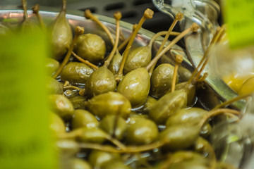 Capers in brine on the background of green leaf.
