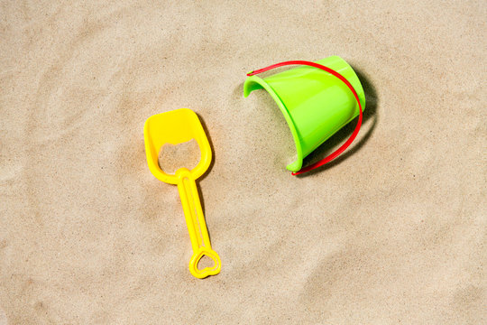 toys, childhood and summer concept - bucket and shovel on beach sand