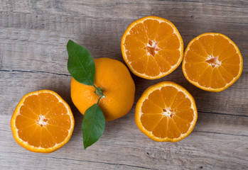 Fresh ripe tangerines with leaves on a wooden background.