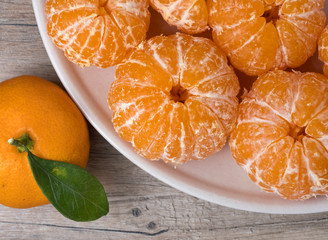 Fresh ripe peeled tangerine in a dish on a wooden background.