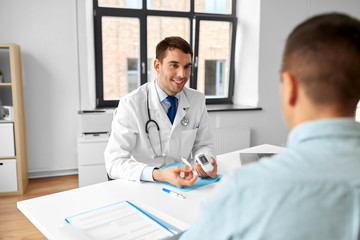 medicine, healthcare and diabetes concept - smiling doctor with glucometer and insulin pen device talking to male patient at medical office in hospital