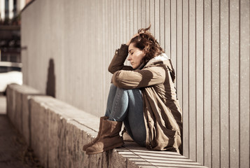Young attractive woman crying suffering from depression sitting