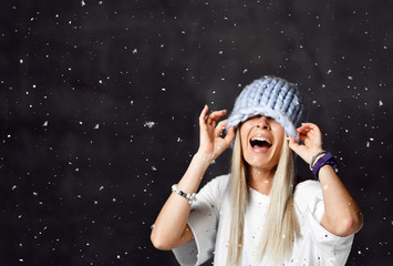Blonde woman in light blue knitted hat happy smiling sitting under snowflakes winter time