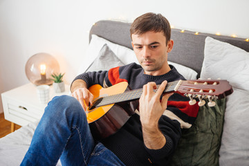 Adult men sitting on bed and plays acoustic guitar