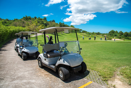 Golf carts parking near golf course with golfers and caddie are in competition,blue cloud sky background.