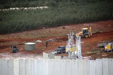 Israeli vehicles are seen from the village of Kfar Kila