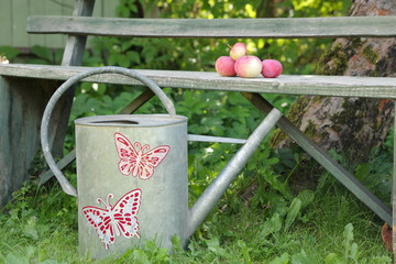 Old garden watering can decorated with a pattern - butterflies, located next to the bench in the garden.