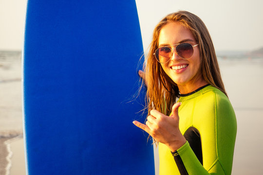 Surfer snow-white smile surfing girl in a stylish wetsuit showing gesture mahalo shaka hand sign signal saying hello on paradise Beach. Female woman holding surfboard smiling happy on Indian Ocean.