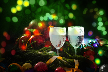 Two glasses of champagne with a Christmas decor in the background