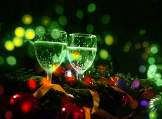 Two glasses of champagne with a Christmas decoration in the background