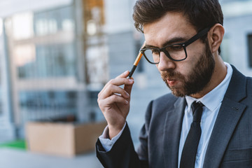 Pensive meditative young businessman in eyeglasses holds a pen in his hand against the background of a business center.