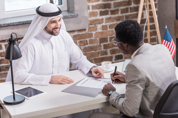 African american businessman signing contract at office desk