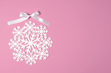 Christmas or winter composition minimal concept. New year bauble or ball made of white snowflakes flat lay on pastel pink background. top view. copy space