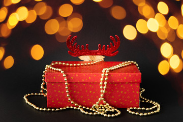 Christmas decoration gift box with hidden reindeer figure on black background with bokeh lights
