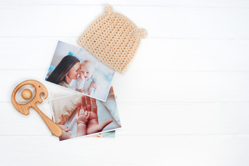 Baby hat, wooden toy and photos on white wooden background
