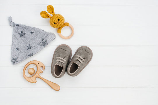Baby hat, booties and wooden toys on white wooden background