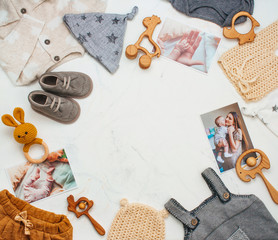 Frame of newborn baby clothing, toys on light marble background