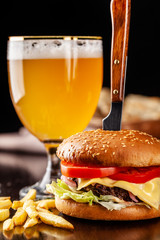 The concept of Italian cuisine. Italian burger with french fries on a wooden board and a glass of light beer with foam. Serving a burger in a restaurant with a knife.