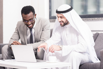 Arabian businessman looking at laptop with african american partner in office