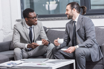 smiling multicultural businessmen sitting on couch, looking at each other and drinking coffee in office